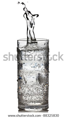 Cube of ice dropped into the glass of sparkling water with splash - stock photo
