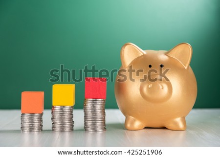 cube wood block on growing coins stack and piggy bank