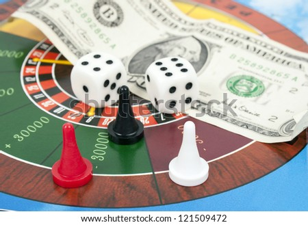 cubes, counters and money on roulette background money - stock photo