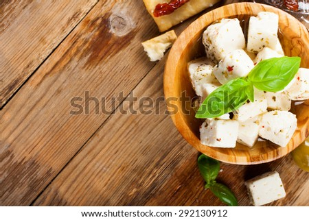 Cubes of feta cheese in olive wood bowl and green and black olives on rustic wooden background.  Selective focus. Food background with copy space. - stock photo