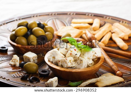 Cubes of feta cheese in olive wood bowl and green and black olives on rustic wooden background.  Selective focus. - stock photo