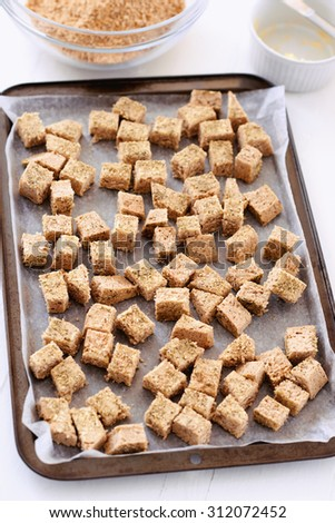 Cubes of leftover wholemeal bread on a baking tray, baked into croutons