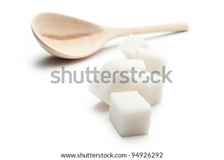 Cubes of sugar with wooden spoon - stock photo