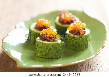 Cucumber appetizers with red caviar and black rice - stock photo