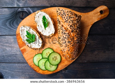Cucumber, baguette with sesame and sandwich with cream cheese and parsley on wooden cutting board - stock photo