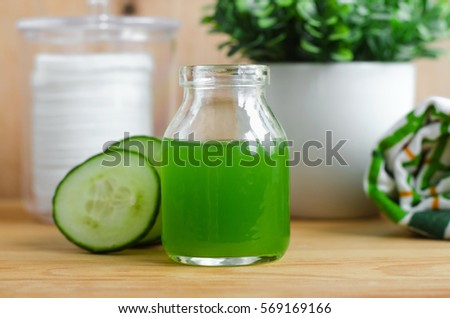 Cucumber juice in a small glass jar for preparing natural facial toner. Homemade cosmetics.