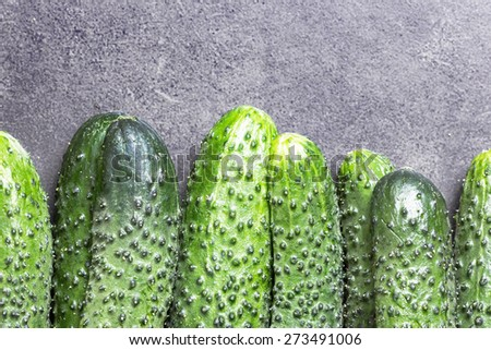 Cucumber on gray black surface texture.