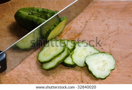 cucumber slices with knife on wood table - stock photo