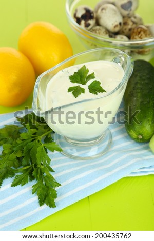 Cucumber yogurt in glass bowl, on color napkin, on color wooden background