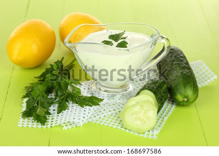 Cucumber yogurt in glass bowl, on color napkin, on wooden background