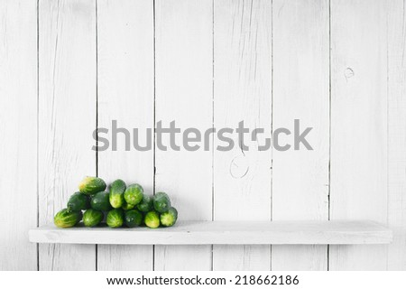 Cucumbers on a wooden shelf. On a wooden, white background. - stock photo