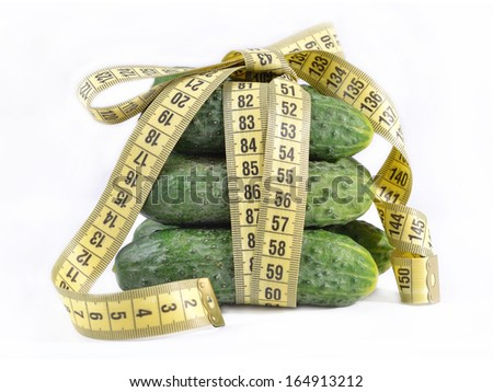 Cucumbers with yellow measuring tape on white background