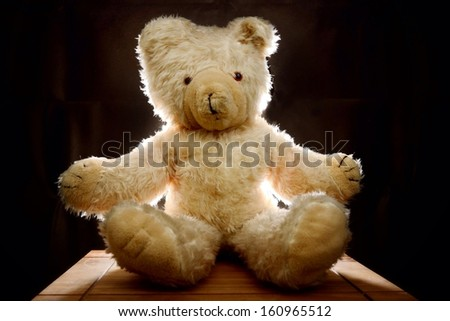 Cuddly teddy bear backlit on dark background - stock photo