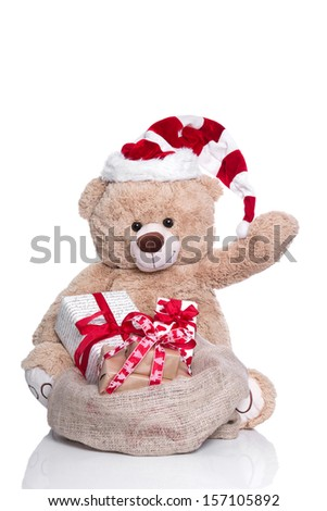 Cuddly teddy bear waving ,wearing Christmas hat and gift boxes on white background - stock photo