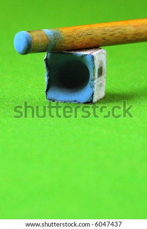 cue stick wit chalk block, shallow depth of field - stock photo