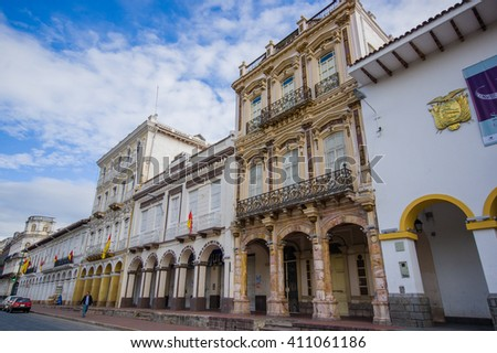 Cuenca, Ecuador - April 22, 2015: Beautiful spanish colonial townhouses with decorated facades, traditional Cuenca architecture and charm, offical city flags hanging - stock photo