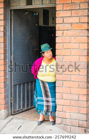 CUENCA, ECUADOR - JAN 9, 2015: Unidentified Ecuadorian woman in a bowler hat near a house. 71,9% of Ecuadorian people belong to the Mestizo ethnic group