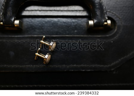 Cuff links on a suit case - stock photo