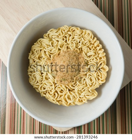 Cuisine and Food, Asian Dried Instant Noodles Blocks with Flavoring Powder for Cooked or Soaked in Boiling Water in White Bowl. - stock photo