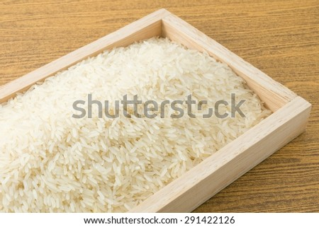 Cuisine and Food, Uncooked White Long Rice, Basmati Rice or Thai Jasmine Rice in A Brown Wooden Tray. - stock photo