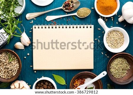 culinary background and recipe book with various spices on wooden table - stock photo