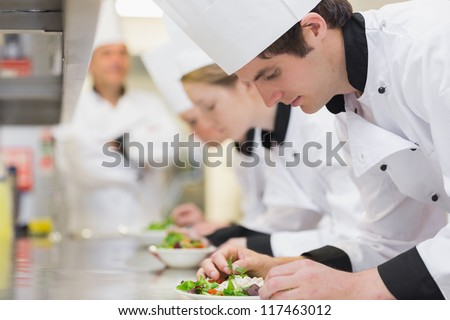 Culinary class in kitchen making salads as teacher is overlooking - stock photo