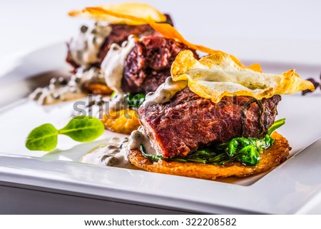 Culinary kitchen. French cuisine. Recipe: Confit pork cheeks with green spinach leaves celery pancakes fried mushroom sauce and fried celery decoration. - stock photo