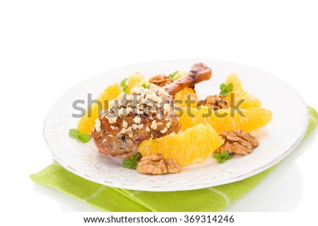 Culinary roast duck with oranges and nuts on plate isolated on white background. Delicious festive eating.  - stock photo