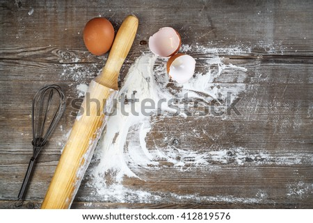 Culinary still life with eggs, eggshells, flour and rolling pin. Vintage cooking background. - stock photo