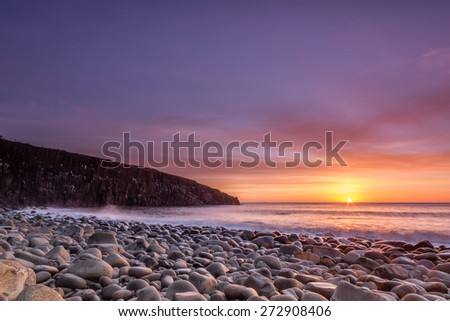 Cullernose Point at sunrise / Sunrise at Cullernose Point in Northumberland with golden clouds lighting the sea washed rocky beach - stock photo