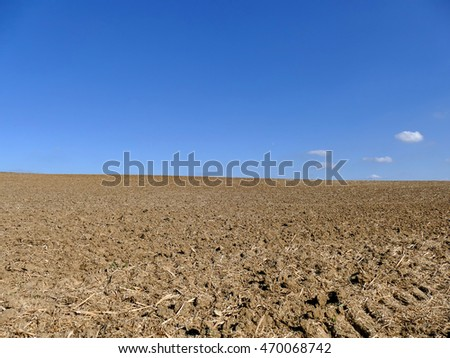 Cultivated plowed field under blue sky and some clouds