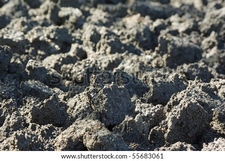 Cultivated soil background in early morning light - stock photo