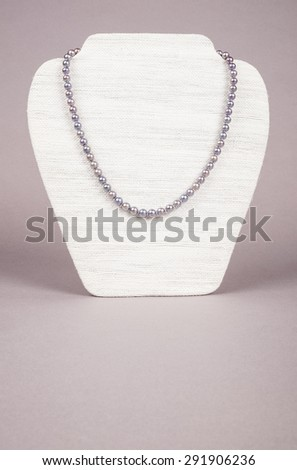 Cultured Black Pearls Necklace on a Display Stand - stock photo
