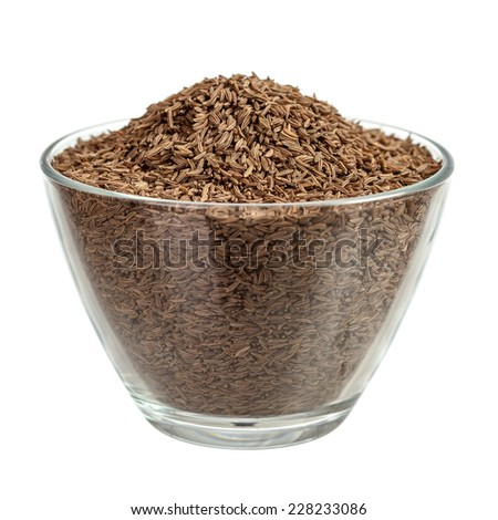 Cumin seeds in glass bowl isolated over white - stock photo