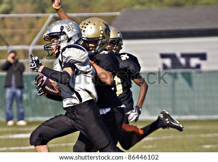 CUMMING, GA - OCTOBER 8: Several unidentified age 11 to 13-year-old  boys run with the ball and block during a football game, the Raiders vs the Saints, on October 8, 2011 in Cumming, GA. - stock photo