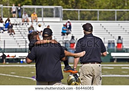 CUMMING, GA - OCTOBER 8 : Unidentified injured player being carried off the field by coaches during a football game; the Raiders vs the Saints, on October 8, 2011 in Cumming, GA. - stock photo