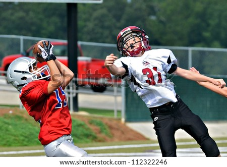 CUMMING, GA/USA - SEPTEMBER 8: Unidentified boy catching the pass at the goal line. Two teams of 7th grade boys September 8, 2012 in Cumming GA. The Wildcats  vs The Mustangs. - stock photo