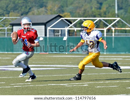 CUMMING, GA/USA - SEPTEMBER 22: Unidentified boy ready to throw a pass during a football game. A team of 7th grade boys September 22, 2012 in Cumming GA. North Forsyth vs Lakeside. - stock photo