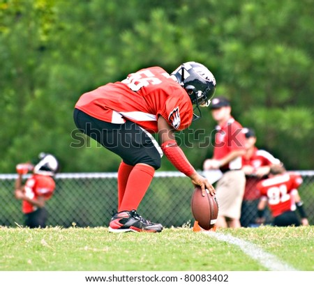 CUMMING, GA/USA - SEPTEMBER 12 : Unidentified kicker placing the football during a baseball game, September 12, 2009 Forsyth County, Cumming GA.  The Broncos vs The Eagles. - stock photo