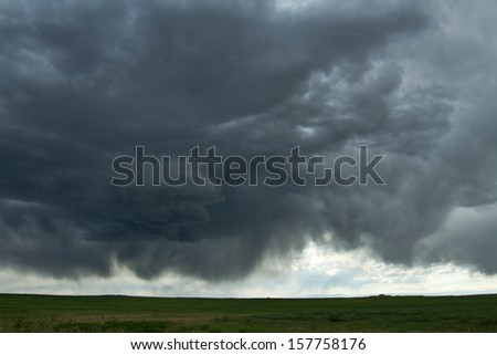 Cumulus clouds and virga of a massive thunderstorm, over a green meadow in Colorado. - stock photo