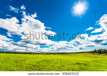 Cumulus clouds over a sunlit hilly fields in the forest - stock photo