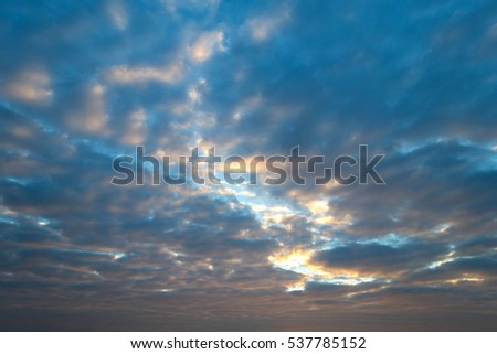 Cumulus sunset clouds with sun setting down on dark background.orange cloud sky and blue sky. Amazing Beautiful skylight.