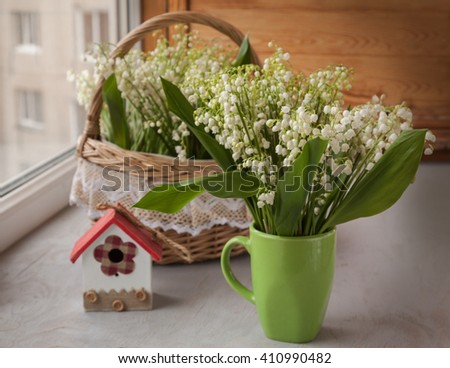 Cup and basket with lilies of the valley (Convallaria majalis) next to decorative birdhouse on o the window - stock photo