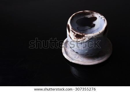 Cup and bowl of traditional Japanese pottery on black background - stock photo