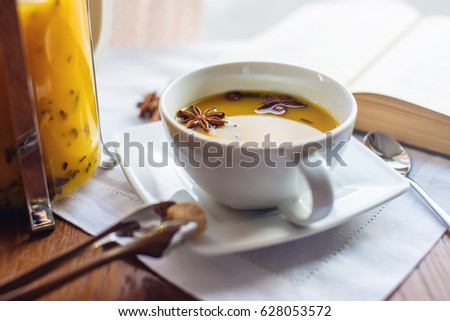 Cup and glass teapot with spicy hot fruit tea with orange and mango next to an open book on table in cafe