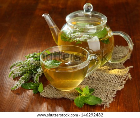 Cup and teapot of herbal tea with fresh mint flowers on wooden table - stock photo