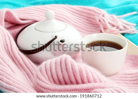Cup and teapot on tray with scarf on fabric background - stock photo