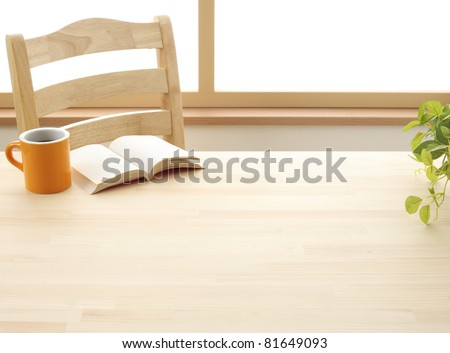 Cup book and plant on wooden table - stock photo