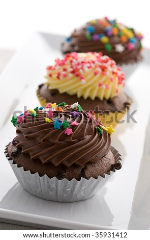 cup cakes on a white plate in a row - stock photo