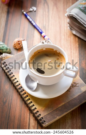 cup coffee and notebook on old wooden table vintage color toned